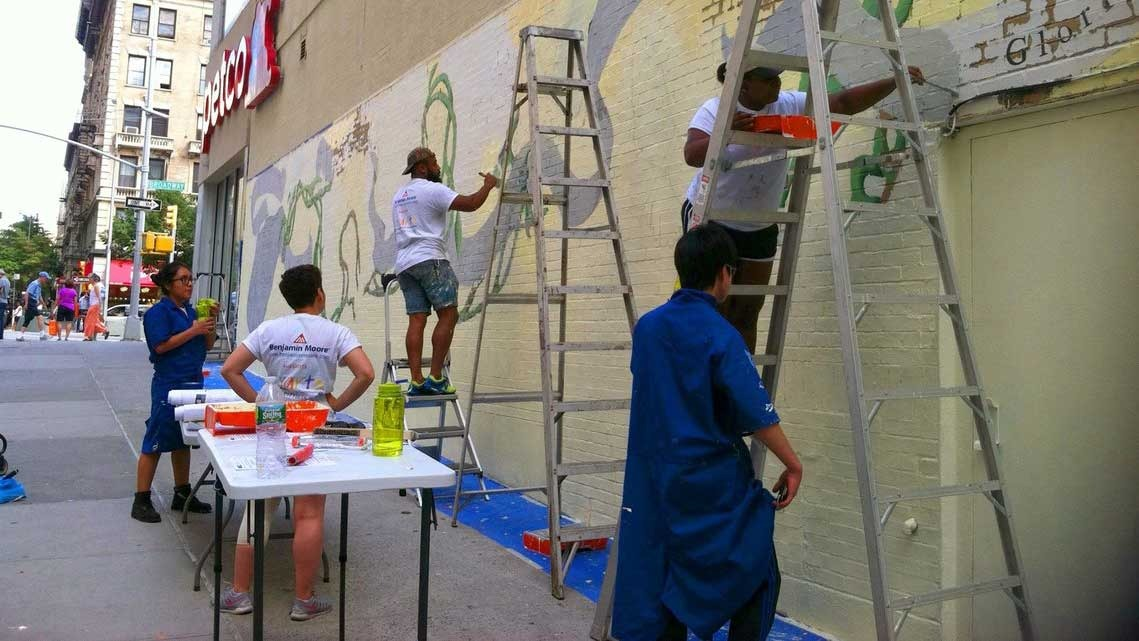 Several people painting a mural on a public wall in New York