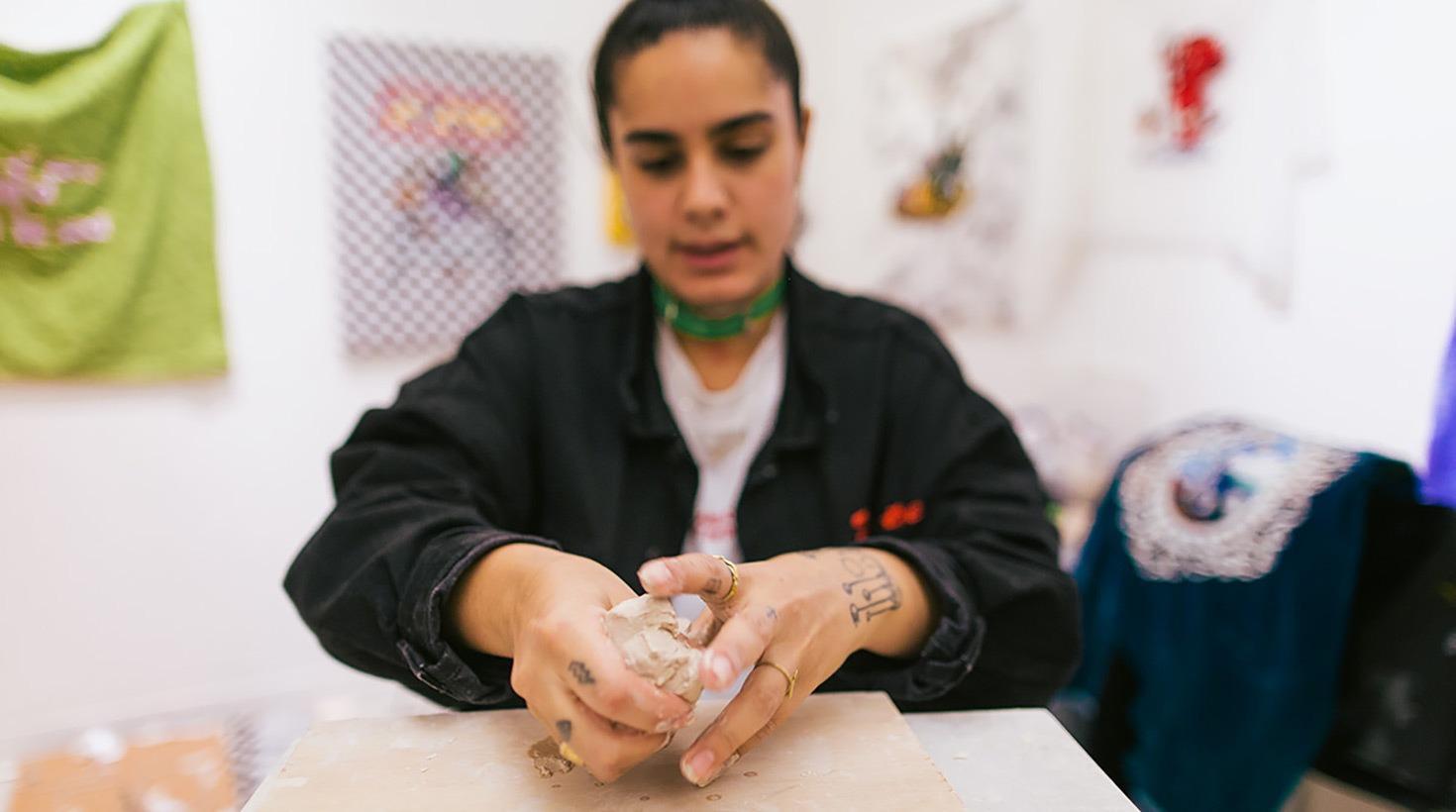 Women preparing clay for a sculpture