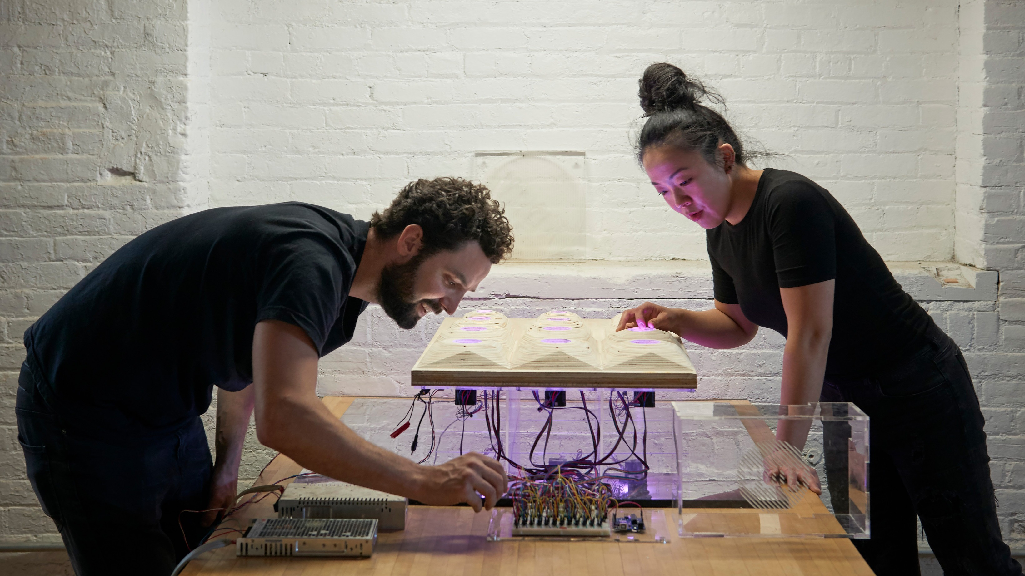 Students wiring an electronic illuminated art piece