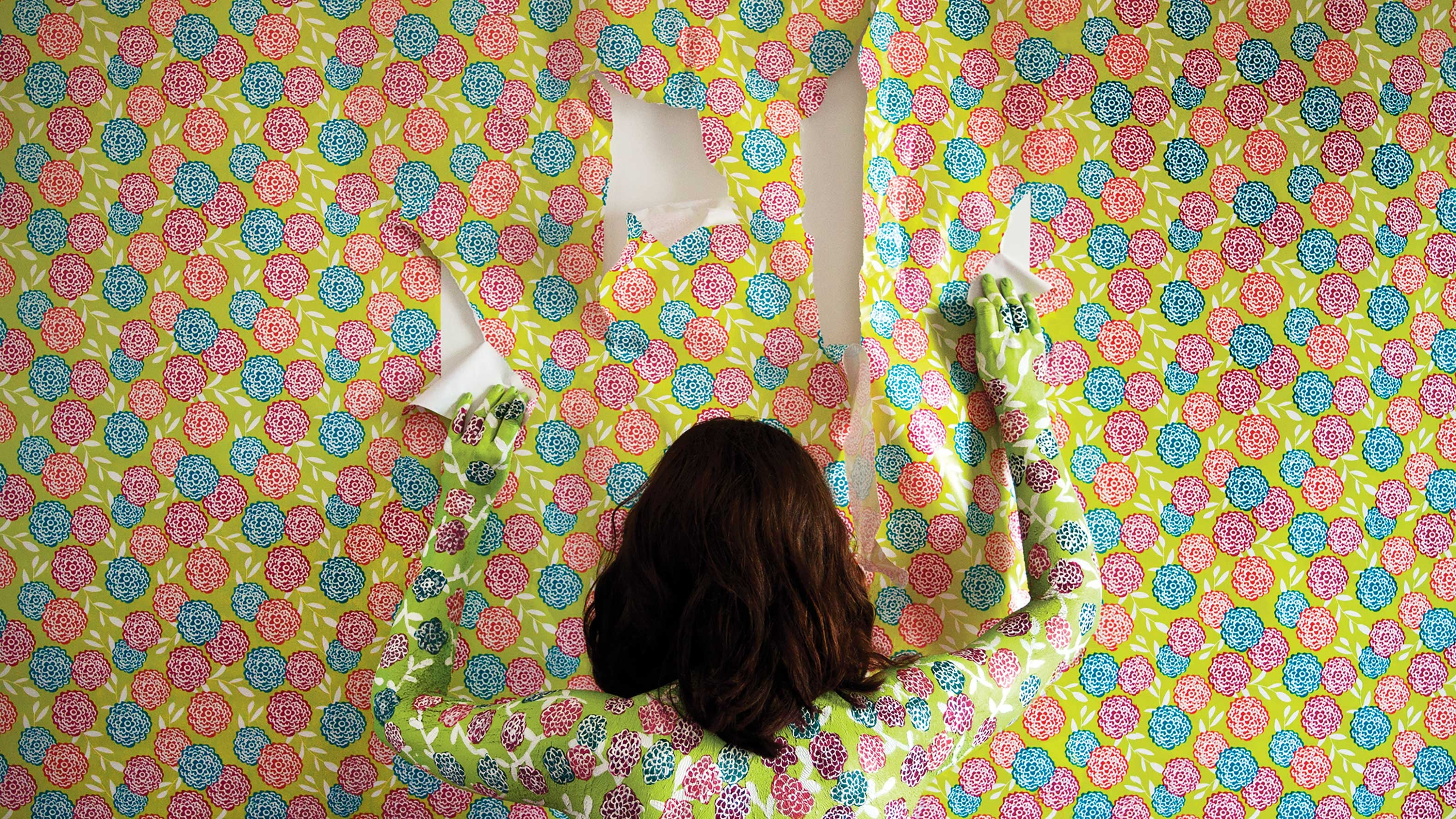 Person facing wall covered in colorful wallpaper.